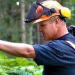 Ein Waldarbeiter, der einen Baum berührt
