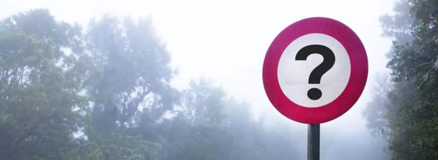 Ein Verkehrsschild mit einem Fragezeichen und im Hintergrund Wald
