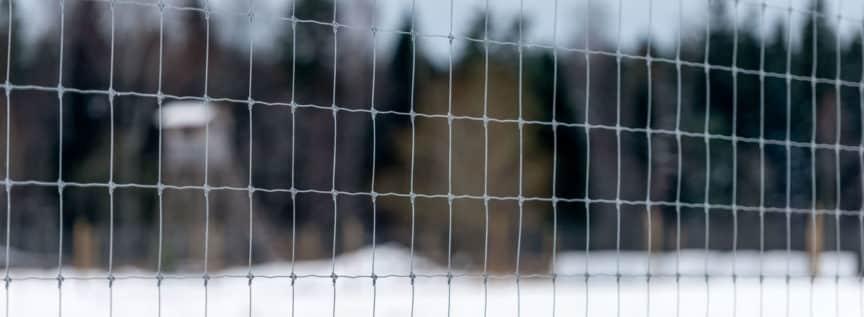 Ein Verbissschutz Zaun mit einem Jagdsitz im Hintergrund